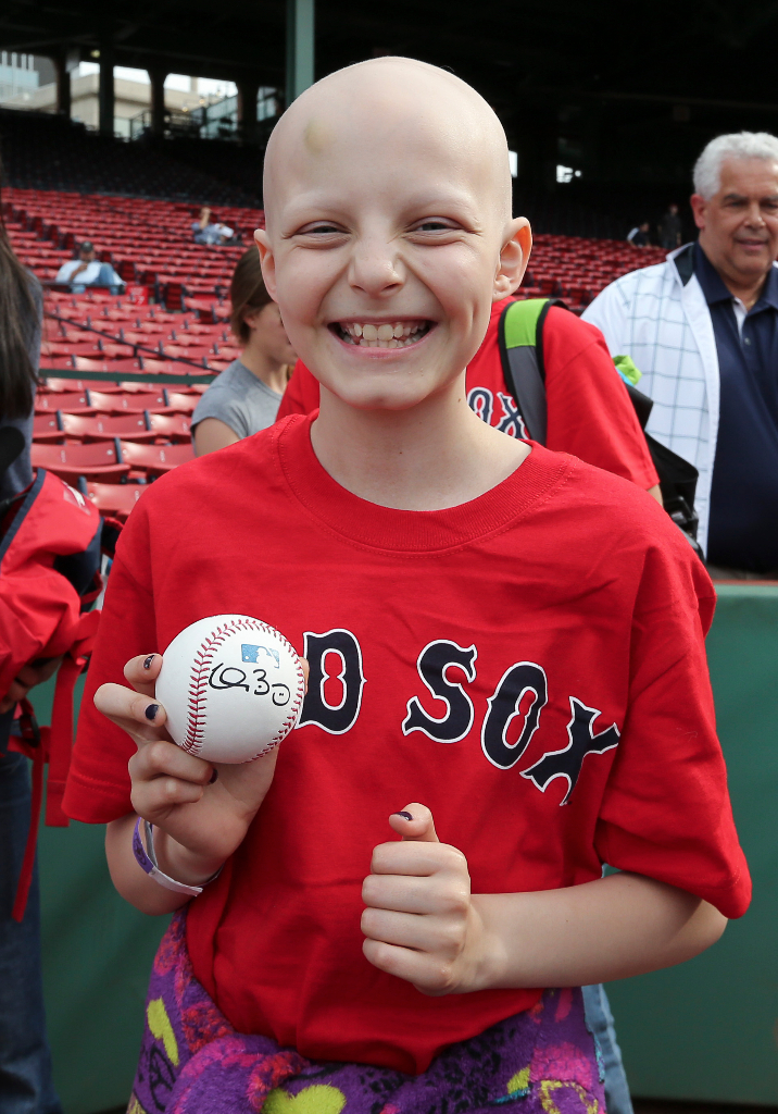 A guest from Christopher's Haven holds onto an autographed baseball given to him during batting practice by Boston Red Sox pitcher Clay Buchholz at Fenway Park in Boston on Wednesday, June 5, 2013. (Brita Meng Outzen/Boston Red Sox)